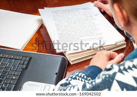 Woman author re-writing her manuscript after it has been proofread by an editor. - stock photo