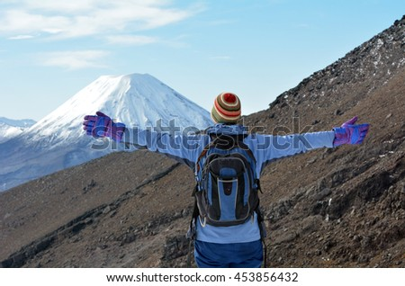 Woman (back view) hike the Tongariro crossing with Mount Ngauruhoe  and Mount Tongariro at the background in Tongariro National Park at the centre of New Zealand's North Island - stock photo