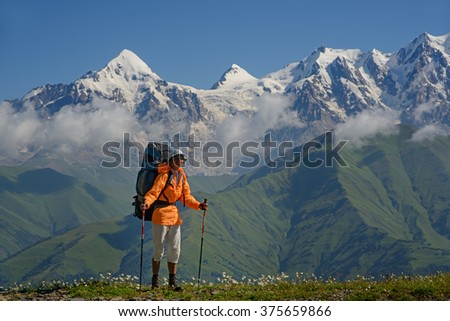 Woman (backpacker) against mountains covered with snow background. Tourist is situated on alpine meadow. Tviber mount is in the left part of photo. - stock photo