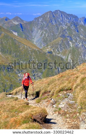 Woman backpacker climbs sunny trail with mountains in the background
