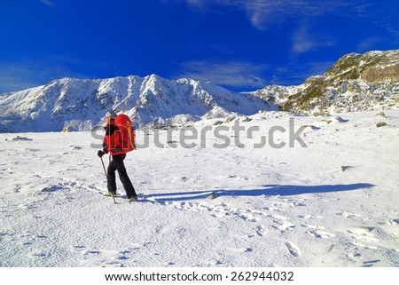 Woman backpacker hiking on snow covered mountain  - stock photo