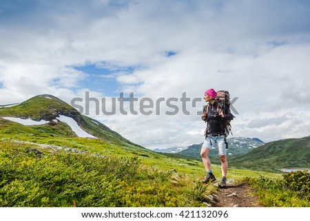 woman backpacker in the mountains enjoy the view. Norway hike - stock photo