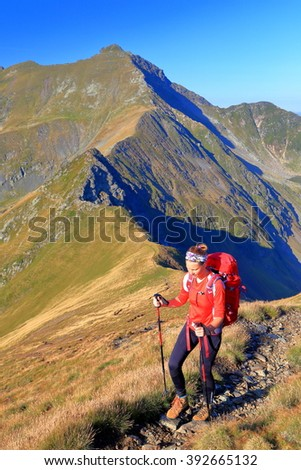 Woman backpacker on aerial mountain trail - stock photo