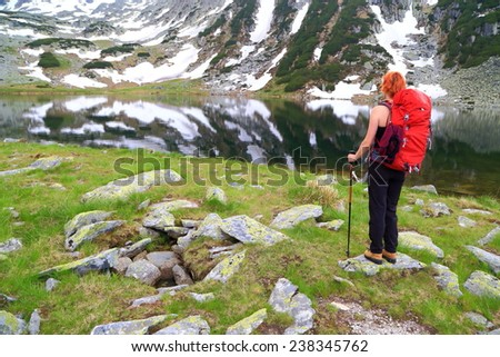 Woman backpacker on the side of glacier lake surrounded by mountains - stock photo