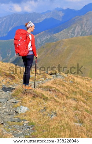 Woman backpacker resting and admiring the view from the mountain trail - stock photo