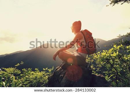 woman backpacker sit on sunrise mountain peak cliff rock enjoy the view - stock photo