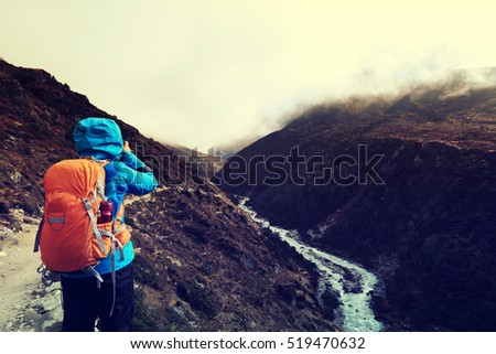 woman backpacker taking photo while trekking at the himalaya mountains