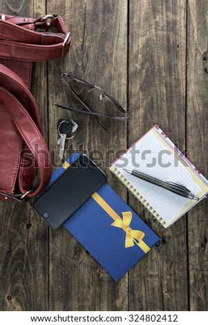 woman bag stuff, handbag over rustic wooden background, from above - stock photo