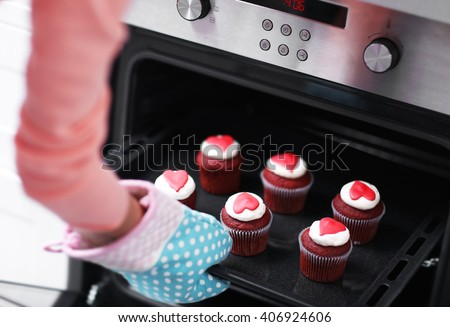 Woman baking cupcakes in the oven - stock photo