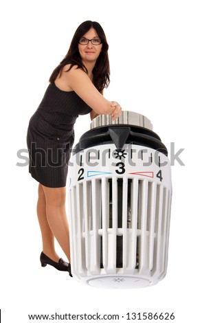 Woman based on a radiator thermostat / heating costs - stock photo