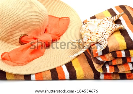 Woman beach hat, bright towel and a seashell isolated on white