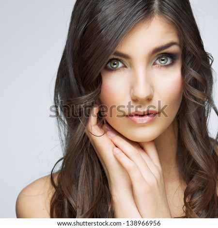 Woman beautiful face portrait. Skin care style face hand touching. Female model studio posing.