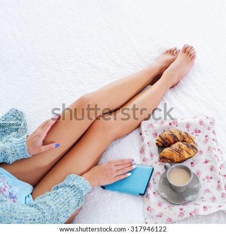 Woman beautiful long legs with pocket book and breakfast in bed top view - stock photo