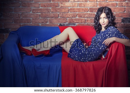 Woman beautiful model on the sofa in the dress in blue and red tones against a brick wall - stock photo