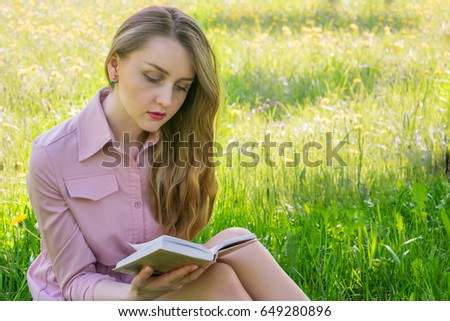 woman beautiful, reading, relaxing at the park, sitting on the grass, summer, sunny day