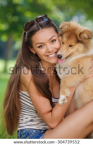 woman beautiful young happy with long dark hair in striped sweater holding dog. Young woman playing with Collie puppy outdoors in the park.