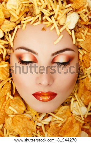 woman beauty face victim of unhealthy eating fast food potato chips rusk frame - stock photo