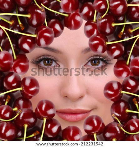 Woman beauty face with cherry frame, close-up - stock photo
