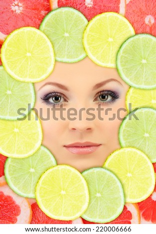 Woman beauty face with fruits frame, close-up - stock photo