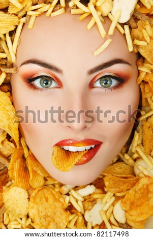 woman beauty face with unhealth eating fast food potato chips rusk frame - stock photo