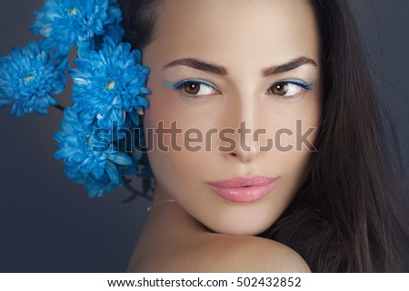 woman beauty portrait with blue flowers close to the head