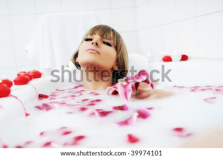 woman beauty spa and wellness treathment with red flower petals in bath - stock photo