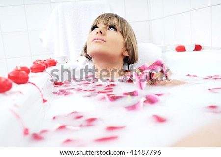 woman beauty spa and wellness treathment with red flower petals in bath with milk - stock photo