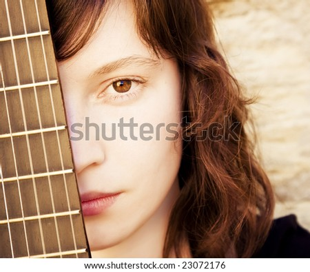 Woman behind fretboard. Square format.
