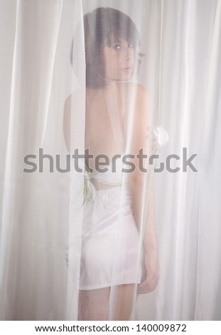 Woman Behind White Sheer Curtain