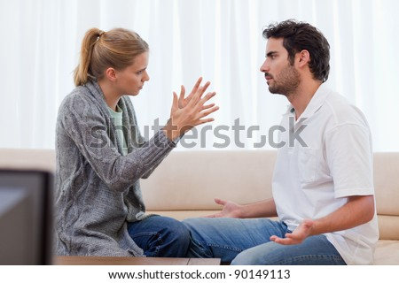 Woman being mad at her boyfriend in their living room - stock photo