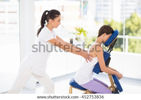 Woman being massaged on chair by masseuse at spa - stock photo