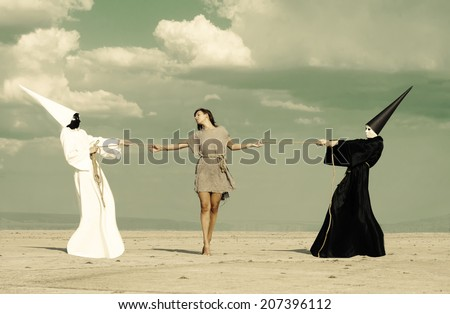 Woman between two mysterious persons playing tug of war - stock photo