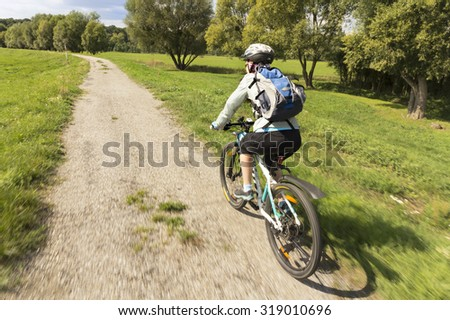 Woman bicyclists riding on country road. Natural motion blur. - stock photo