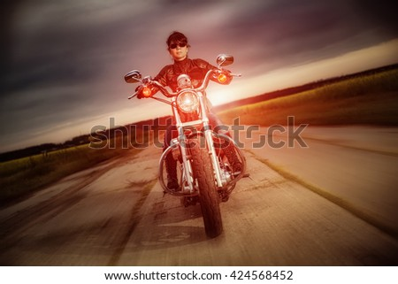 Woman biker in sunglasses and leather jacket racing on a motorcycle on the road. Filter applied in post-production. - stock photo