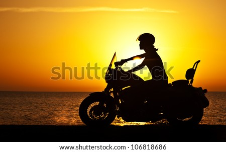 Woman biker over sunset, female riding motorcycle, motorbike driver traveling, girl racing on the beach road, freedom lifestyle - stock photo