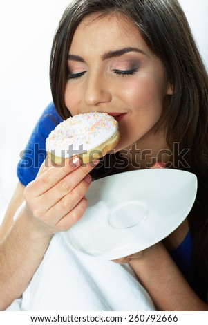 Woman bite donut. Close up portrait of young woman holding plate with donut. - stock photo