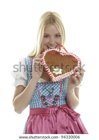 Woman bites in an empty German Gingerbread heart - stock photo