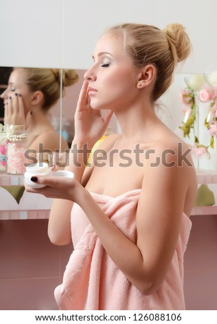 Woman blonde puts on face a cream - stock photo
