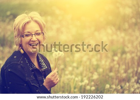 Woman blowing dandelion - stock photo
