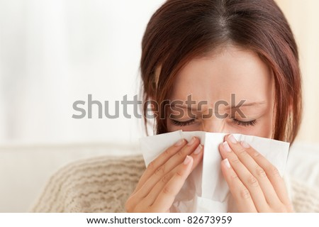 Woman blowing her nose in a living room - stock photo