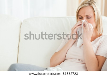 Woman blowing her nose in her living room - stock photo