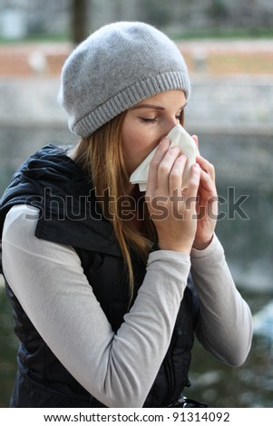 Woman blowing into tissue