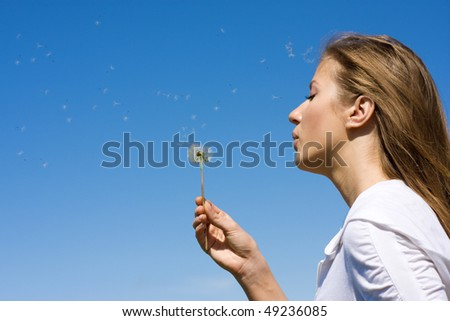 Woman blowing on white dandelion at blue sky - stock photo