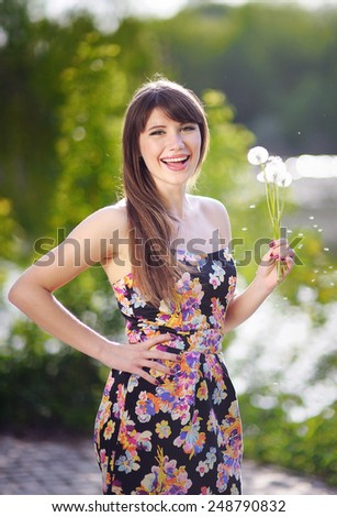 Woman blows dandelions in the park. Concept of nature and rest. - stock photo