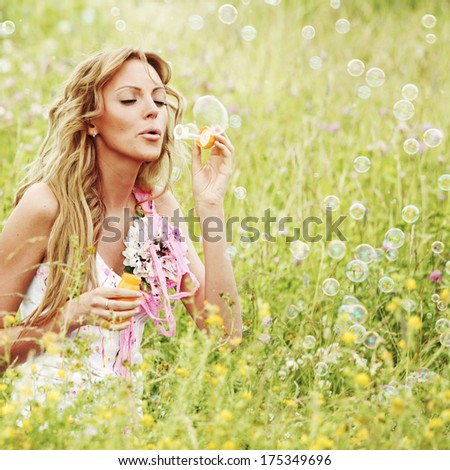Woman blows soap bubbles on flower field - stock photo