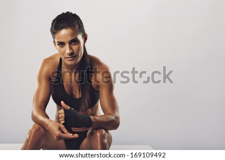 Woman boxer wearing black strap on wrist for boxing practice, Fitness female sitting getting ready for boxing practice. Beautiful young woman with muscular body preparing for workout. - stock photo