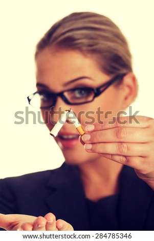 Woman breaking cigarette to stop smoking.