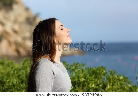 Woman breathing fresh air relaxed on vacation with the beach in the background       - stock photo