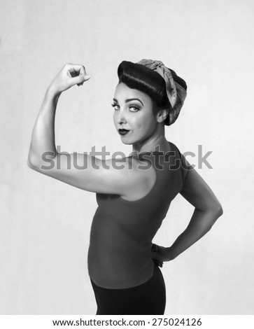 woman brunette in a blue shirt with a scarf on her head and hair in a retro style biceps show-off