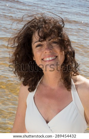 Woman brunette with curly hair on the beach - stock photo